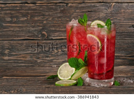 red cocktail with mint, lime and ice on dark wooden background with space for your text - stock photo