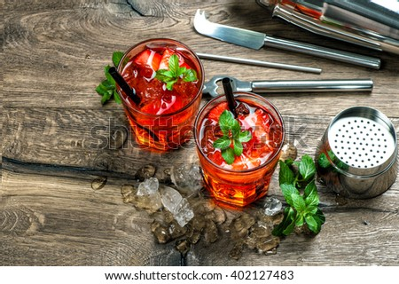 Red cocktail with strawberry, mint leaves, ice. Drink making bar accessories on wooden table. Alcoholic drink. Alcoholic cocktail.  - stock photo
