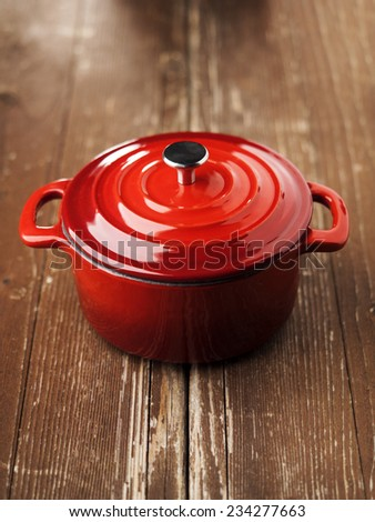 Red cocotte pot on brown wooden table with cover lid - stock photo