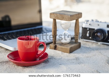 Red Coffe Mug and Vintage hourglass with silver laptop and old camera in the sand at the beach - stock photo