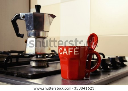 red coffee cup and  vintage coffeepot on kitchen stove - stock photo