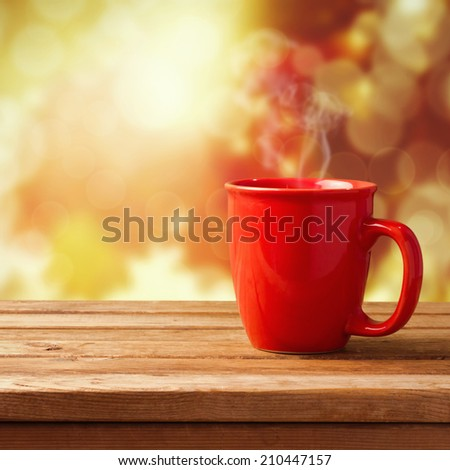 Red coffee cup over autumn background - stock photo