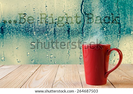 """red coffee cup with smoke on water drops glass window background with text """"Be right back"""" - stock photo"""