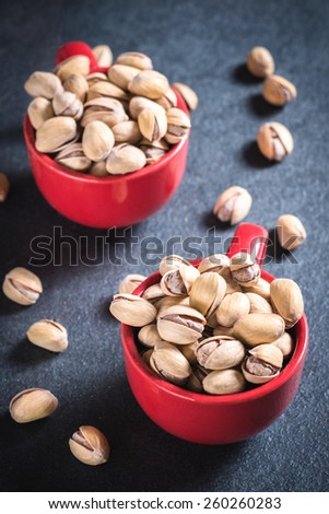 Red coffee cups stuffed with pistacios snack,selective focus  - stock photo