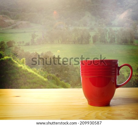 Red coffee mug overlooking a green farmland - stock photo