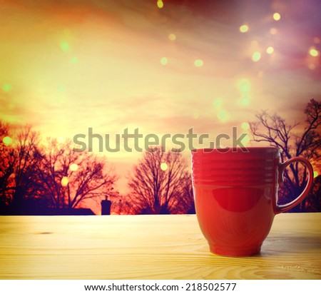 Red Coffee Mug Overlooking a Twilight Scene  - stock photo
