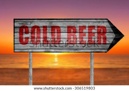 Red Cold Beer wooden sign with on a beach background - stock photo
