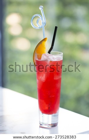 Red color cocktail decorated with piece of orange serve on marble table - stock photo