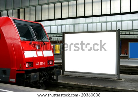 Red commuter train at railway station with blank billboard - stock photo