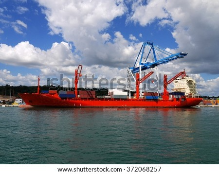 Red Container Ship alongside loading containers at container terminal. - stock photo