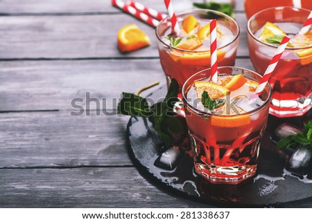 Red cool cocktail with oranges, soda, raspberry syrup, mint leaves on dark wooden table. Selective focus. Toned image - stock photo