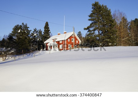 red cottage in a snowy winter landscape, Sweden - stock photo