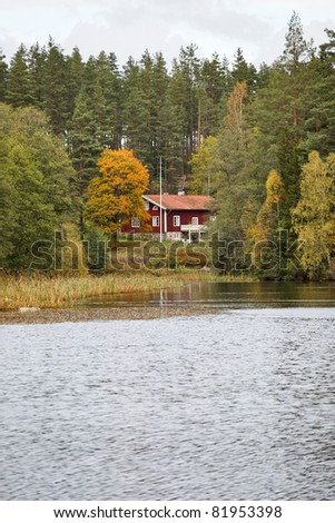Red cottage in the forest at the lake - stock photo