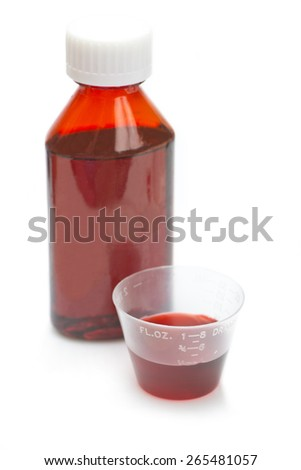 Red cough and cold liquid cold medicine in measuring cup on white. - stock photo