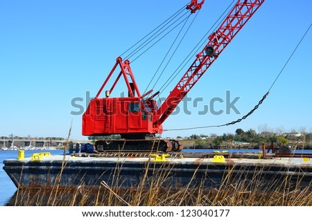 Red crane along the shore to do some heavy lifting - stock photo