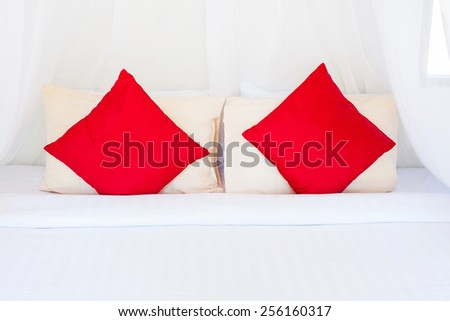 Red/Cream pillows on a bed Comfortable soft pillows on the bed - stock photo