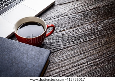 Red cup of coffee and laptop.vintage tone Retro filter effect,soft focus,low light.(selective focus) - stock photo