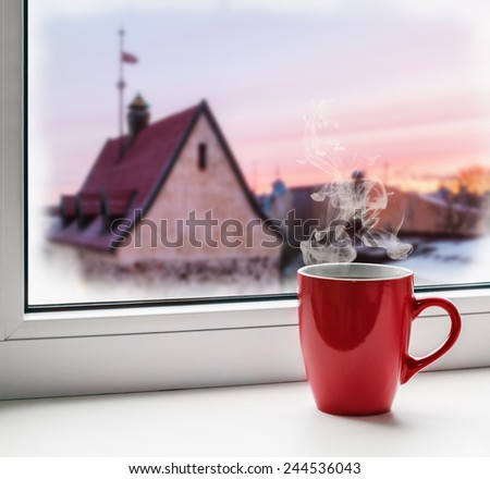 red cup of coffee on the windowsill  - stock photo