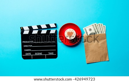 red cup of coffee, slapstick and money in the envelope on the blue background - stock photo