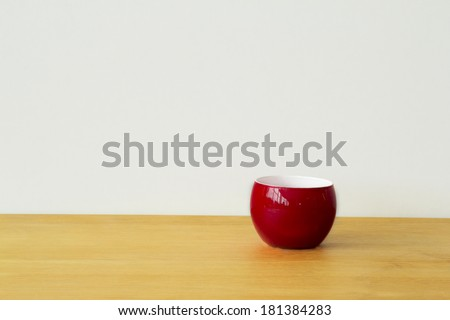 Red cup on a brown wood table - stock photo