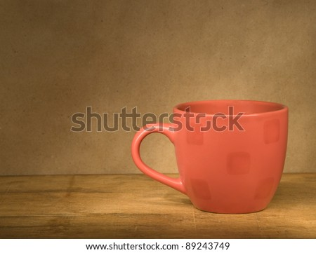 Red cup on the old wooden table against gray wall. - stock photo