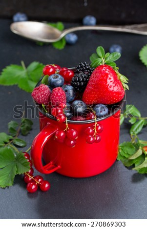 red cup with fresh ripe berries on black stone background, low key - stock photo