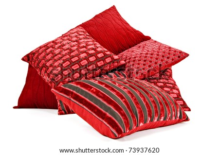Red cushions stacked up on a white background with space for text - stock photo