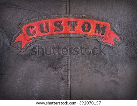 Red custom label on back of leather jacket in close-up. - stock photo