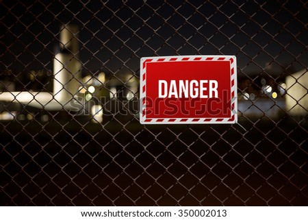 Red Danger sign on private property hanging on a chainlink fence during night - stock photo