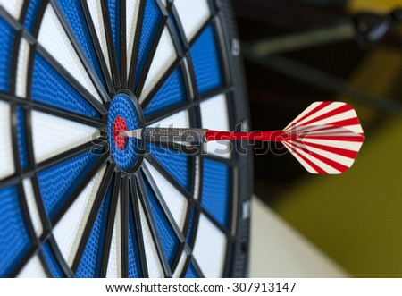 red darts arrows in the target center - stock photo