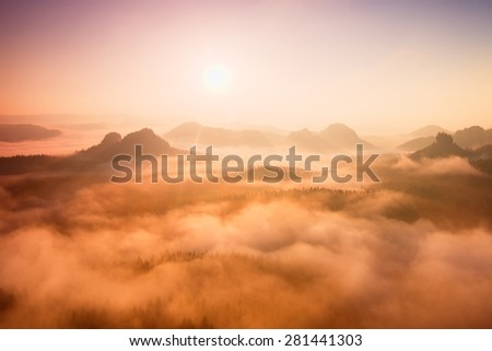 Red daybreak. Misty daybreak in a beautiful hills. Peaks of hills are sticking out from foggy background, the fog is red and orange due to Sun rays.  - stock photo