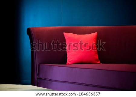 Red decorative pillow on a contemporary sofa. - stock photo