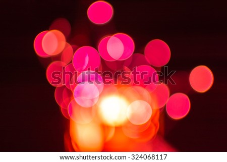 Red defocused bokeh Christmas lights on a wooden support - stock photo