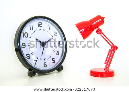 Red desk lamp focusing on alarm clock on white background - stock photo