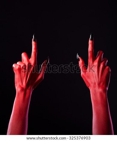 Red devil hands pointing fingers up, Halloween theme   - stock photo
