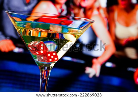 red dice in the cocktail glass in front of gambling table, casino series - stock photo