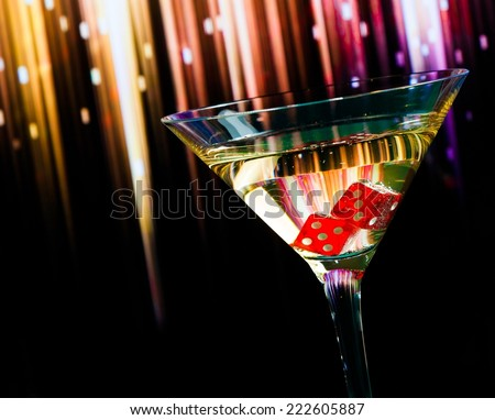 red dice in the cocktail glass on colorful gradient background - stock photo