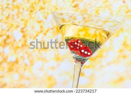 red dice in the cocktail glass on golden background - stock photo