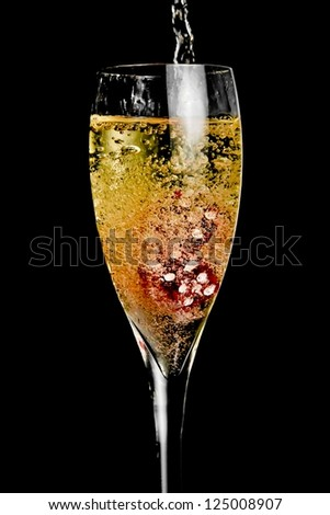 red dice in the glass of champagne being filled with a lot of bubbles on black background - stock photo