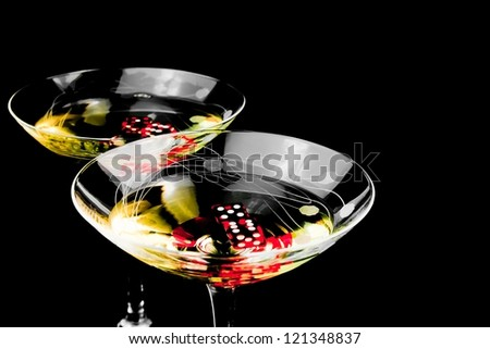 red dice in two cocktail glasses on black background - stock photo