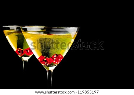 red dice in two cocktail glasses with gold bubbles on black background with space for text - stock photo