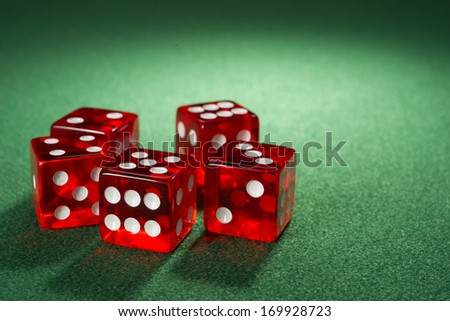 Red dice on a green felt - stock photo