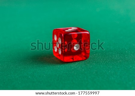 Red dice on green felt - stock photo