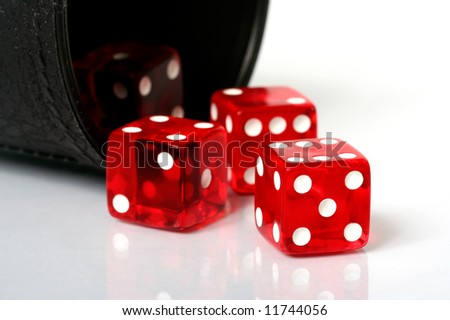 Red dice thrown from dice cup onto white background - stock photo