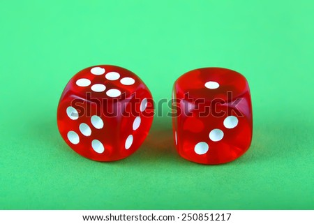 Red dices on green background - stock photo