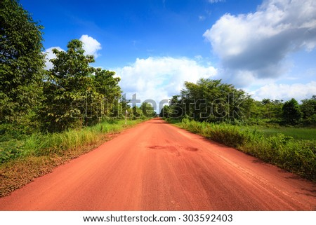 Red dirt road in the tropical jungle - stock photo