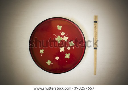 Red dish and chopsticks with oriental style on a white background  - stock photo