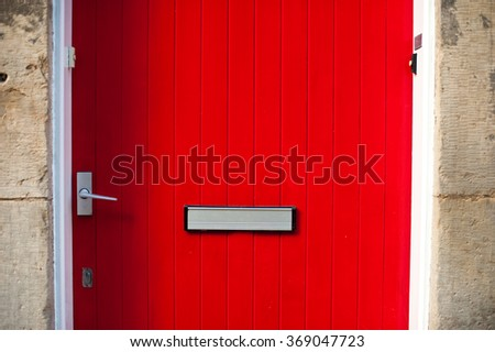 Red door in a stone building - stock photo