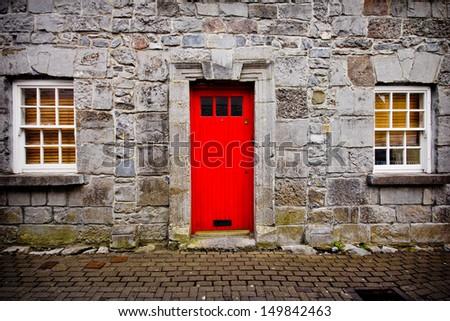 Red door on old European stone house - stock photo