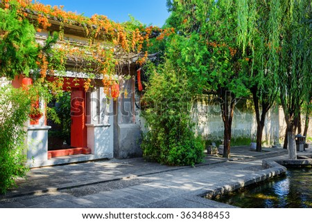 Red doors leading into courtyard of traditional Chinese house in Dali Old Town, Yunnan province, China. Beautiful view of street with flowers and green trees at the ancient city. - stock photo